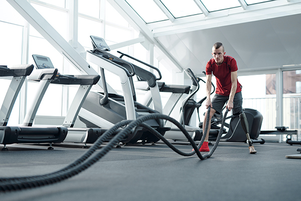Man with prosthetic leg using ropes at gym