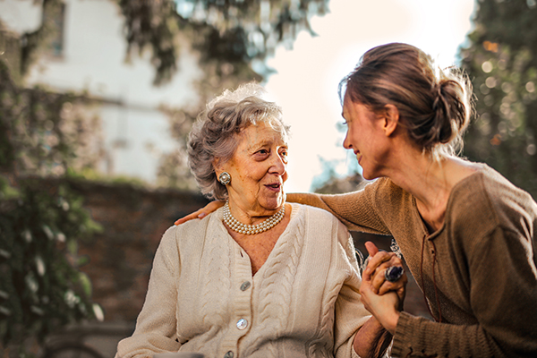 Woman smiling while holding elderly woman's hand